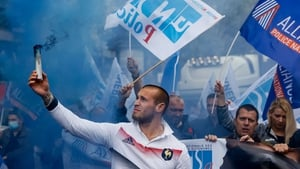 A demonstrator holds a flare during a protest of members of French police unions including Alliance Police Nationale on the Champs-Élysées