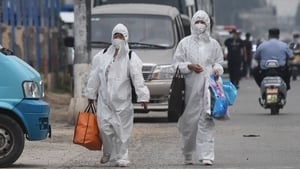 Two women wearing protective suits in Beijing, China after 11 residential estates were locked down
