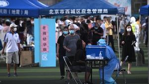 Beijing residents who live near Xinfadi market queue for a coronavirus test