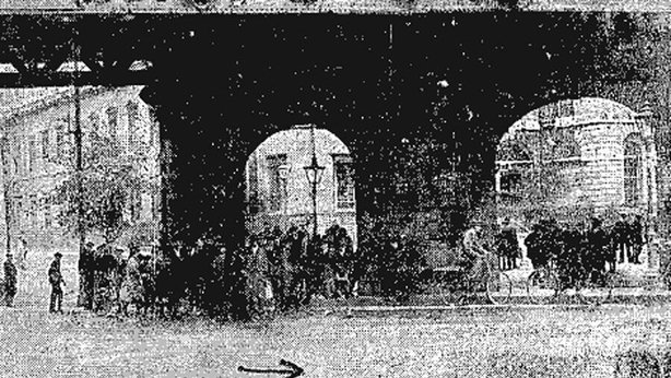 Crowds gather around the site of the shooting on Beresford Place in Dublin City. The arrow shows the direction the car escaped Photo: Freeman's Journal, 23 June 1920