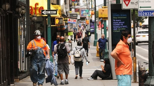 People walk through Manhattan as the city prepares to enter stage 2 of reopening on Monday