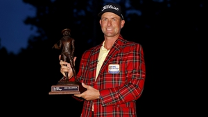 Webb Simpson of the United States celebrates with the trophy and tartan jacket