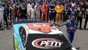 Bubba Wallace stands by his car after NASCAR drivers pushed him to the front of the grid