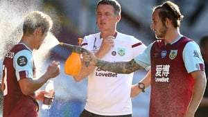 Burnley's Josh Brownhill (R) sprays water at team-mate Ashley Westwood during a drinks break