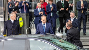 Taoiseach-elect Micheál Martin is applauded by party colleagues as he leaves the Convention Centre