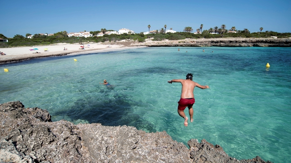 A man jumps into the sea at an almost empty beach in Menorca, Spain