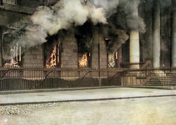 Flames emerge from the Custom House in 1921 in this image colourised by John Breslin