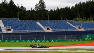 Lewis Hamilton steers his car past empty stands during the first practice session