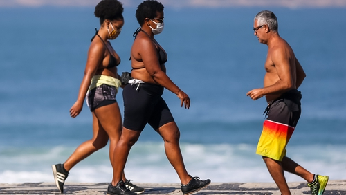People wearing face masks walk along Ipanema beach in Rio de Janeiro, Brazil