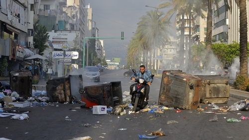 A motorcyclist rides through a blockade in Beirut during a demonstration against the economic conditions