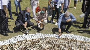 Volunteers installing the sea of ceramic cups in a meadow next to the Srebrenica memorial centre