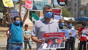 Syrian protesters in Idlib carry placards expressing their opposition to regime ally Russia's attempt to reduce cross-border aid