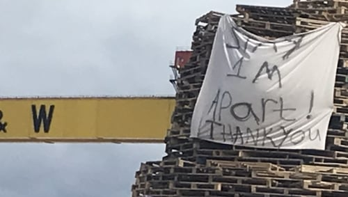 A sheet with the message 'Stay 1m apart thank you' on a bonfire pile in Belfast as Orange Order asked for no bonfires to be lit due to coronavirus