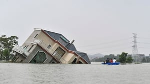 Residents ride a boat past a damaged house near the Poyang Lake in China's central Jiangxi province