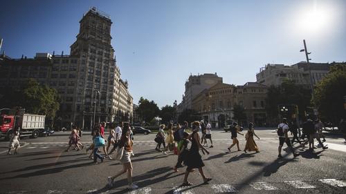 People cross the Gran Via de Les Corts Catalanes in Barcelona