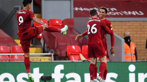 Trent Alexander-Arnold (R) celebrates scoring with team-mates Andrew Robertson (centre) and Roberto Firmino