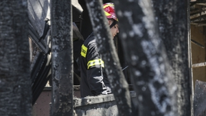 A firefighter pictured walking through the ruins in the days after the fire tragedy