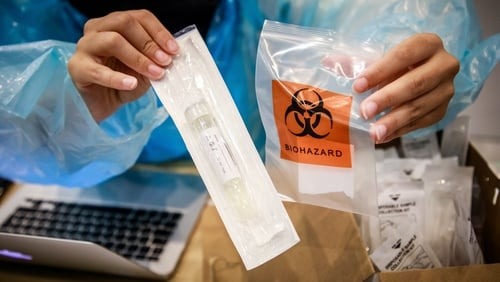 A health worker handles a swab sample collected from a traveller for testing at Paris-Charles de Gaulle Airport
