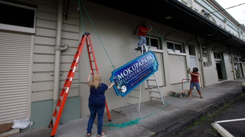 Citizens in Hilo, Hawaii remove signage in preparation for Hurricane Douglas