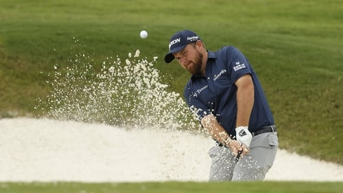 Shane Lowry plays a shot from a bunker on the 16th hole
