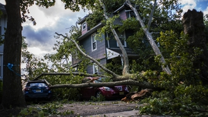 A house and cars damaged by fallen trees in New Jersey
