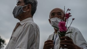 A man holds a flower as he queues to pray in remembrance of the victims of the Hiroshima bombing