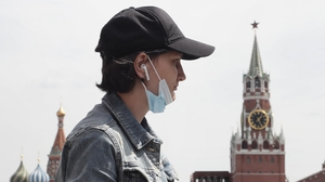 A woman wearing a lowered protective face mask walking on the Red Square in Moscow this week