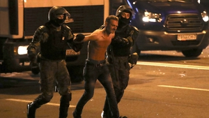 Riot police detain a man participating in a protest