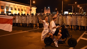 A couple rides a scooter in front of riot police during a protest after polls closed in Belarus' presidential election