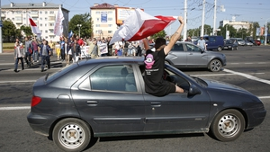 An opposition supporter waves an old Belarusian national flag from a car window in Minsk