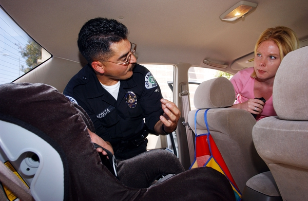 A police officer conducts a seat belt and child safety check with motorists.