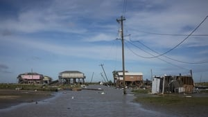 Damaged homes sit among flood water