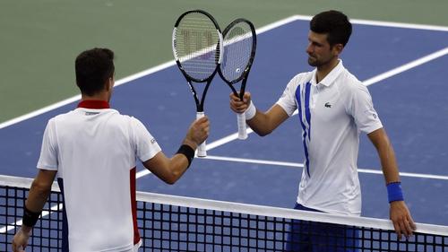 Novak Djokovic (R) taps racquets with Roberto Bautista Agut after defeating him