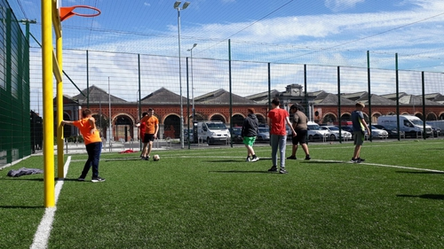 Children who are part of the Just Ask youth club play football near Greek Street flats