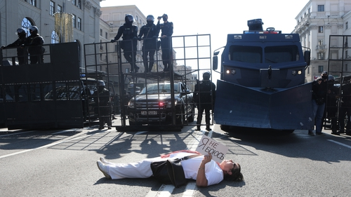 A woman lies down in front of police in Minsk, Belarus, holding a sign that says 'I am not afraid'