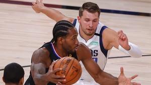 Kawhi Leonard #2 of the LA Clippers drives against Trey Burke #32 and Luka Doncic #77 of the Dallas Mavericks