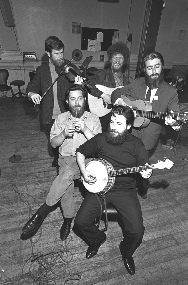 John Sheahan, playing the violin/fiddle, Luke Kelly smiling and playing the guitar and Ronnie Drew playing the guitar. From left to right seated at the front are Ciarán Bourke playing the tin whistle and Barney McKenna playing the banjo.