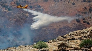 A firefighting plane drops water to extinguish the flames in Greece