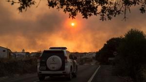 A Civil Guard patrol car in El Buitron in Huelva as smoke billows from a wildfire