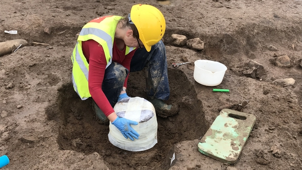 Specialist archaeological conservator Susannah Kelly wraps the urn in bandages to protect it for its removal