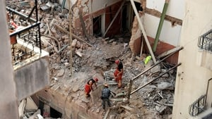 Rescue workers at the site of the collapsed building where a pulse was detected