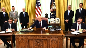 Donald Trump watches as Kosovar Prime Minister Avdullah Hoti (R) and Serbian President Aleksandar Vucic sign an economic agreement