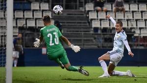 Lyndon Dykes lifts the ball over the Czech goalkeeper