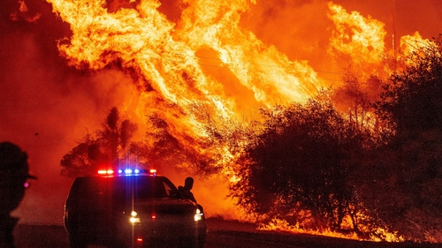 A law enforcement officer watches flames launch into the air as fire continues to spread during the Bear fire in Oroville, California today