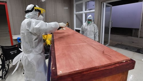 A hospital worker nails down the coffin of Covid-19 victim in an Indonesian hospital