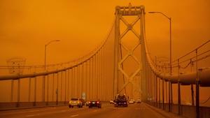 Cars drive along the San Francisco Bay Bridge under an orange smoke filled sky in San Francisco San Francisco