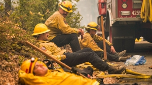 Firefighters Rob Spitzer, Max Kitty, Josiah Gist, and Hunter Grossmann with Cal Fire Madera Mariposa Merced Unit - Rancheria take a break along Waterfall Way in the Cascadel Woods community where he and his colleagues have been fighting the Creek