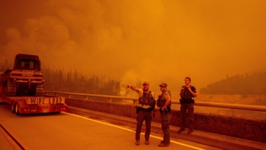 Law enforcement and fire personnel wait on the Enterprise Bridge to enter an area encroached by fire in Butte County
