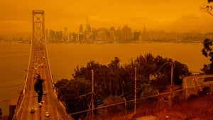 Jose Castillo has his photo taken with the Bay Bridge and the San Francisco skyline in the background by his friend Laito Miyake, both of San Francisco, as smoky skies from the northern California wildfires casts an orange and yellow color in San Francisc