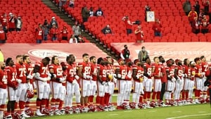 Members of the Kansas City Chiefs link arms before a sparse crowd at Arrowhead Stadium
